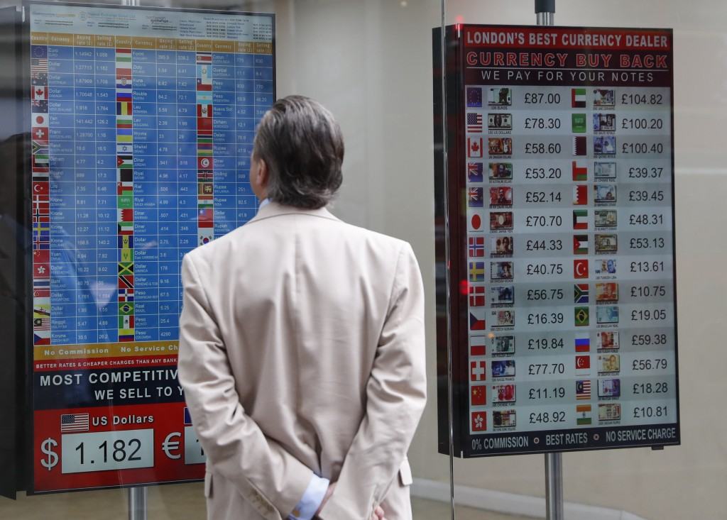 A man looks at a currency exchange rate list at a currency exchange bureau, on a main shopping street in London, Tuesday, July 30, 2019. The pound has