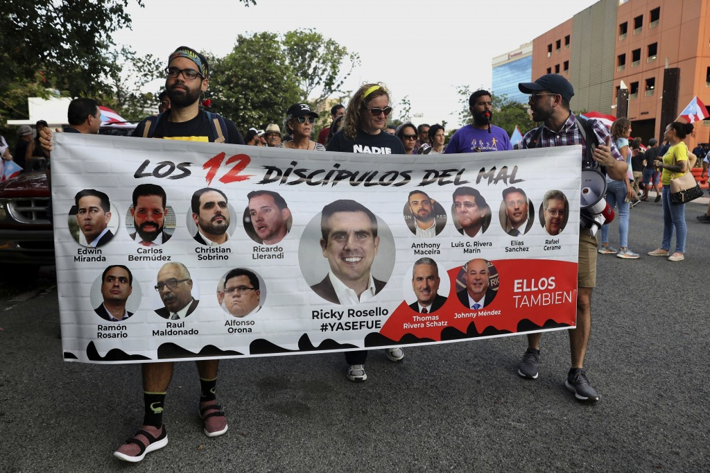 "Protesters hold a banner featuring resigned Gov. Ricardo Rosselló, center, amid other politicians that reads in Spanish ""The 12 disciples of evil. The..."