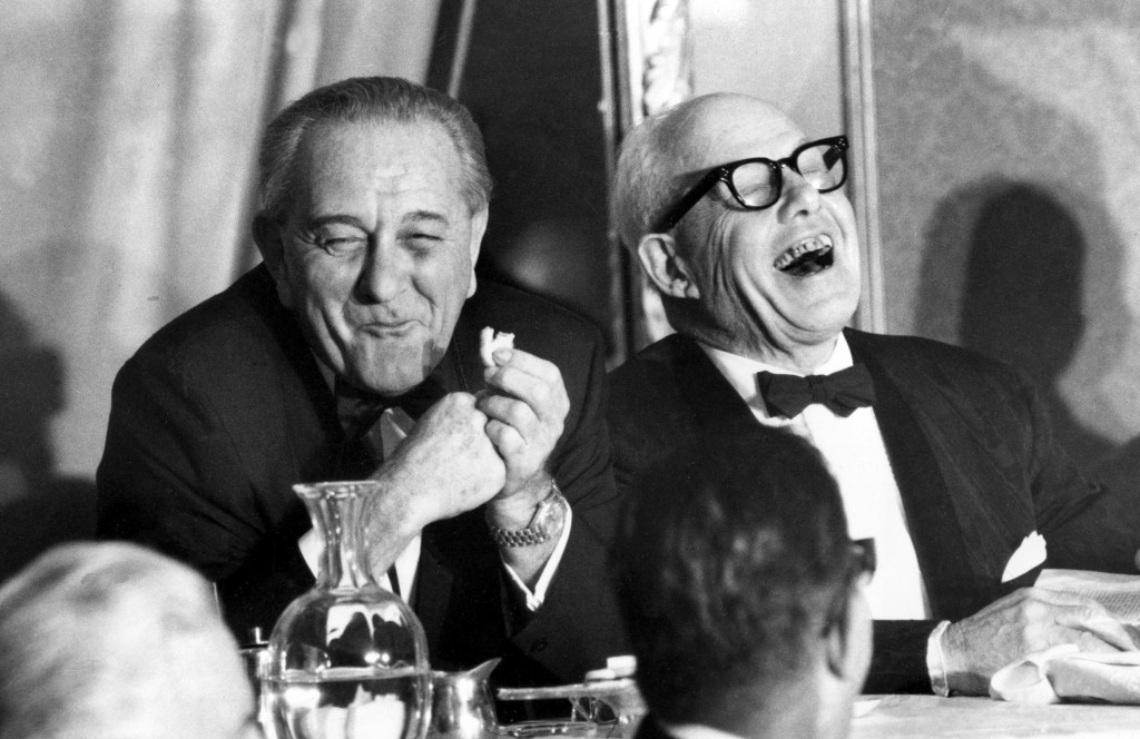 FILE - In this Nov. 9, 1967, file photo, U.S. President Lyndon B. Johnson, left, munching on a cookie, and George Meany, president of the AFL-CIO, lau...