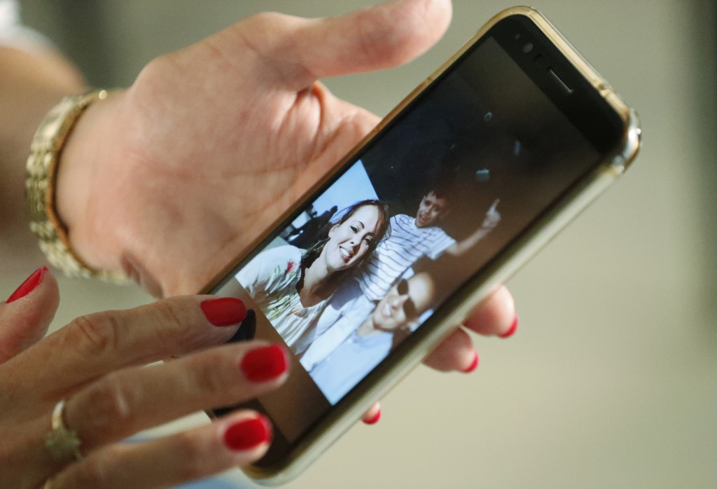 In this June 20, 2019 photo, Mary Sardinas, 60, shows a photo of her son, daughter-in-law and grandson in Cuba as she speaks during an interview with ...