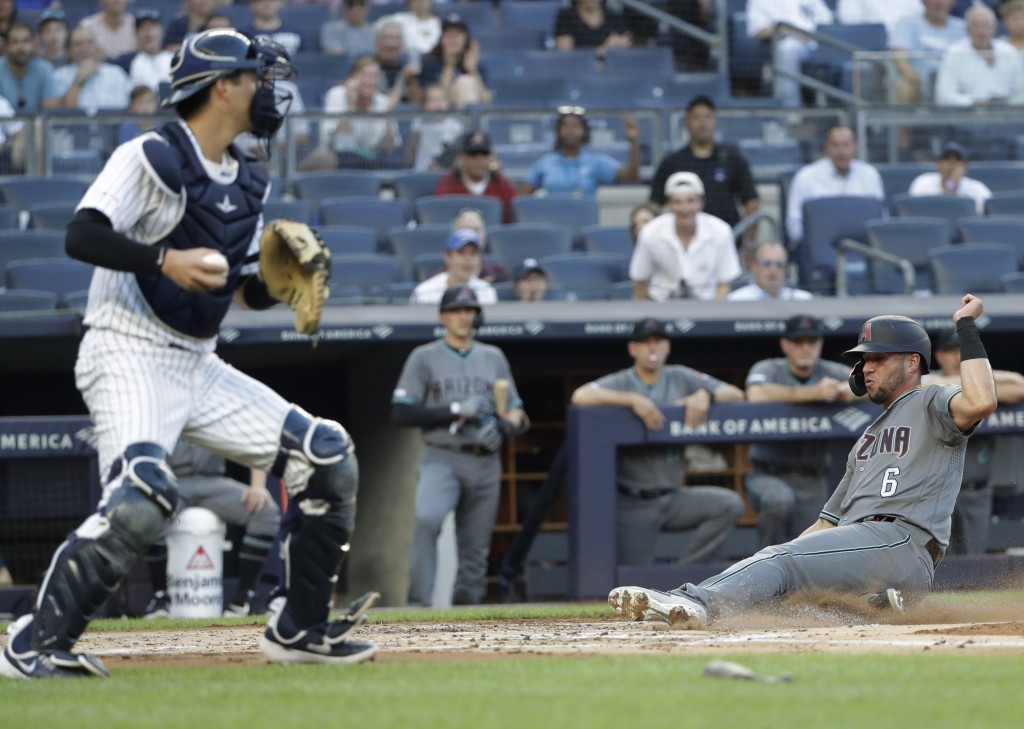 Arizona Diamondbacks' David Peralta (6) slides in to score on a sacrifice fly by Adam Jones, next to New York Yankees catcher Kyle Higashioka during t