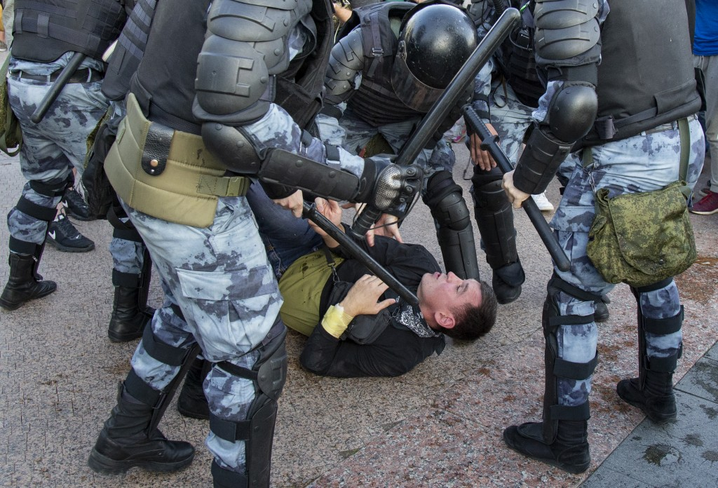 In this photo taken on Saturday, July 27, 2019, police officers detain a person during an unsanctioned rally in Moscow. The protest was the latest in ...