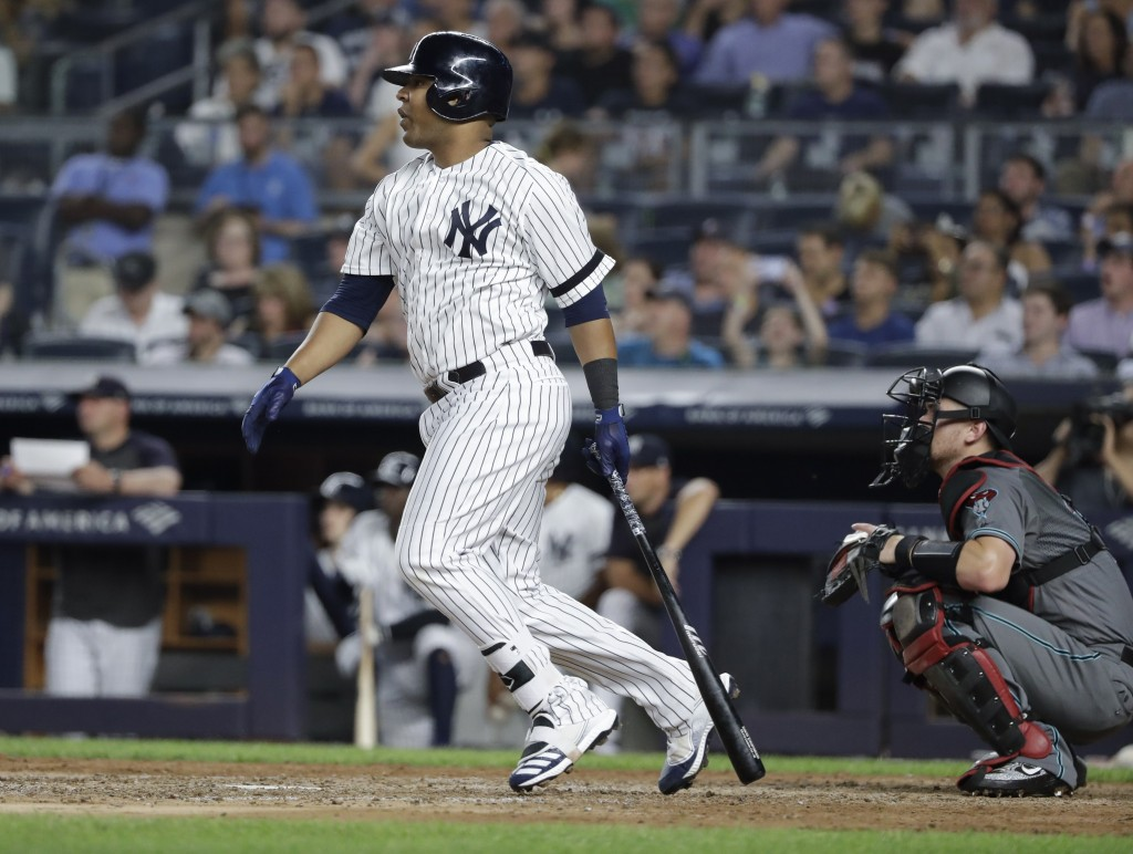 New York Yankees' Edwin Encarnacion follows through on an RBI double during the sixth inning of the team's baseball game against the Arizona Diamondba...