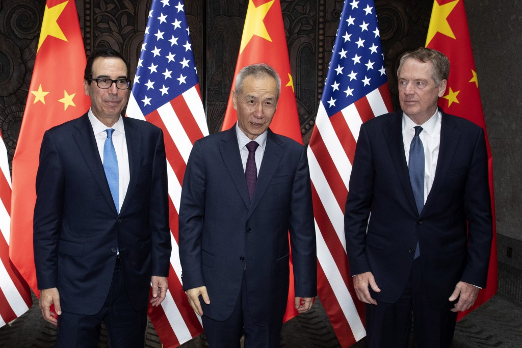 Chinese Vice Premier Liu He, center, poses with U.S. Trade Representative Robert Lighthizer, right, and Treasury Secretary Steven Mnuchin, for photos ...
