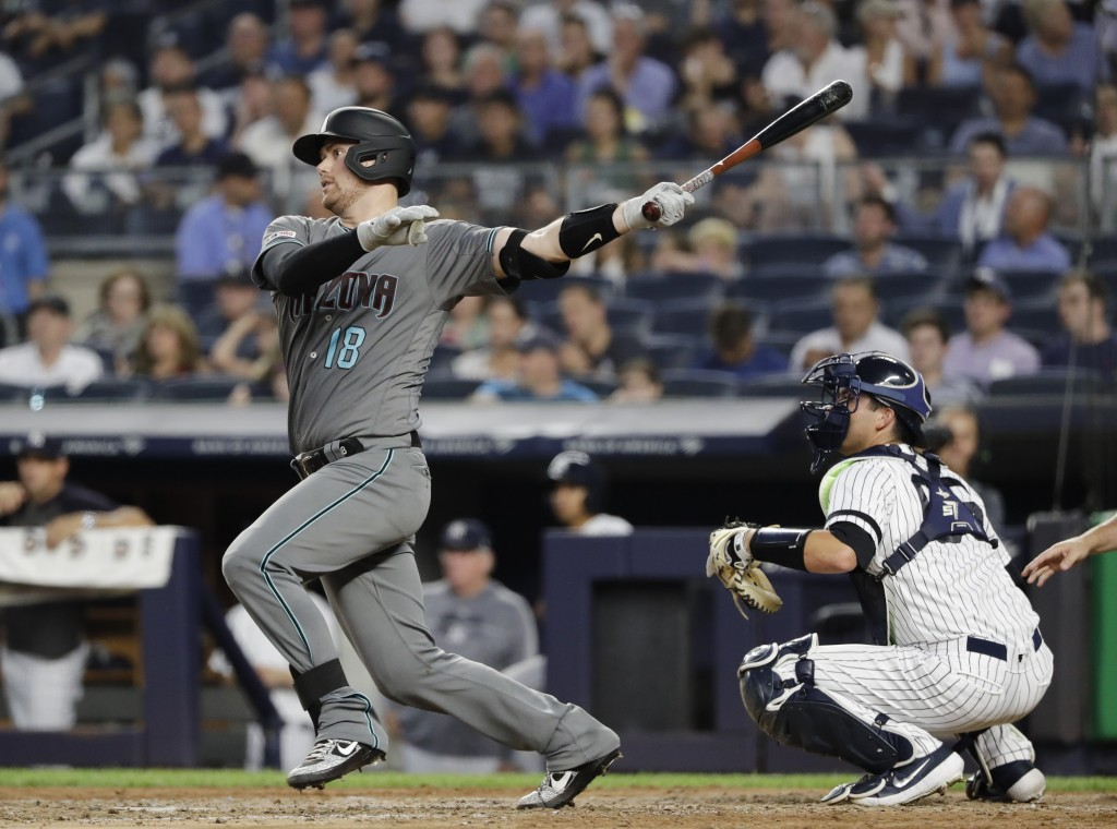 Arizona Diamondbacks' Carson Kelly follows through on a single during the fourth inning of a baseball game as New York Yankees catcher Kyle Higashioka