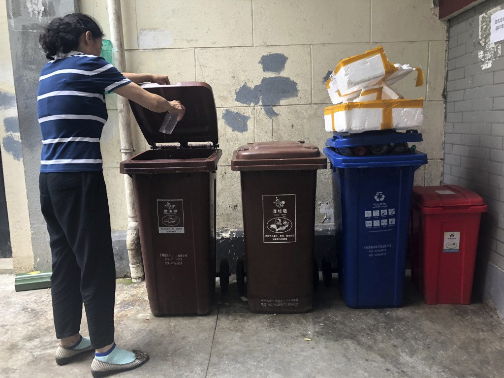 In this  July 22, 2019, photo, a resident pours kitchen wash in a garbage container marked for wet garbage in a residential community in Shanghai. Chi...