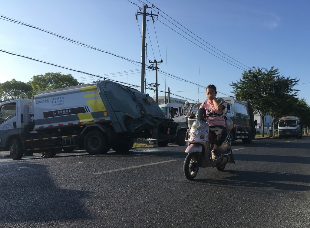 In this  July 23, 2019, photo, a woman on a motorcycle covers her mouth as she passes by a line of trash collection trucks waiting to enter a trash st...