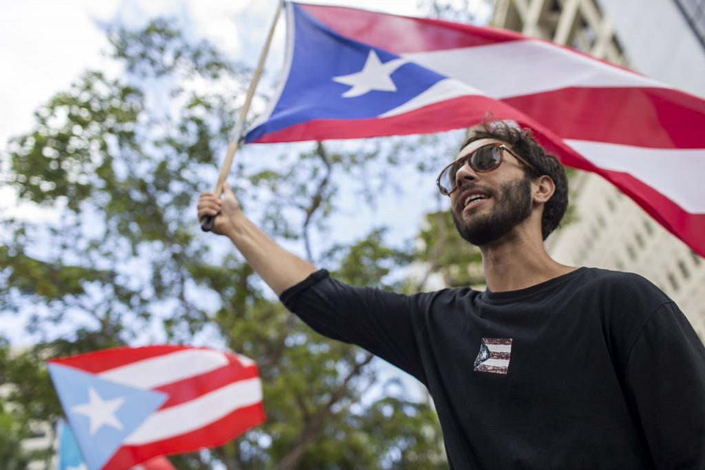 In this July 25 photo, a demonstrator flies a Puerto Rico flag as people gather to celebrate the resignation of Gov. Ricardo Rossello who announced th...