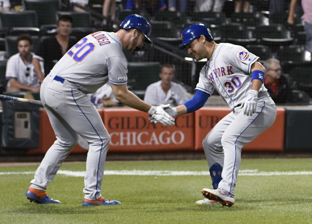 New York Mets' Michael Conforto (30) is greeted by Pete Alonso (20) after hitting a home run against the Chicago White Sox during the 11th inning of a