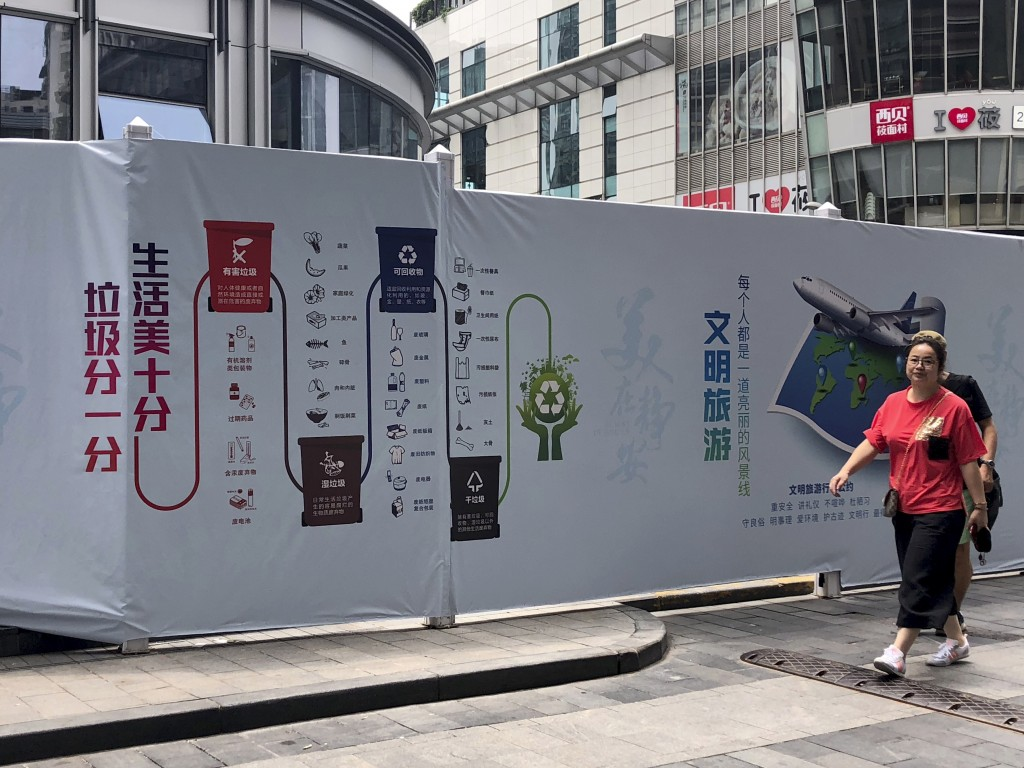 In this July 22, 2019, photo, a woman walks past a publicity board highlighting waste separation and recycling regulations in downtown Shanghai. China...
