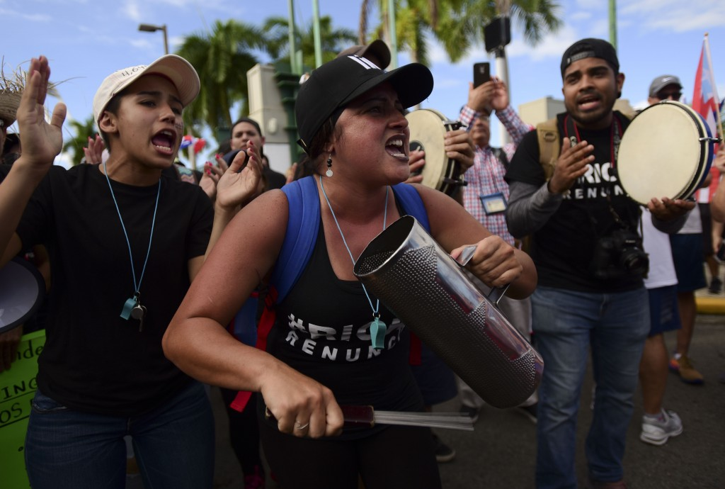FILE - In this July 22, 2019 file photo, demonstrators play on percussion instruments as they march on Las Americas highway demanding the resignation ...