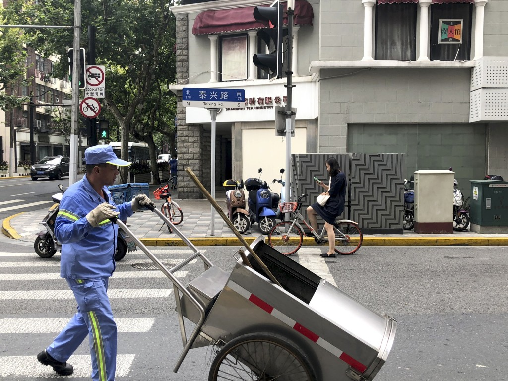 In this July 22, 2019, photo, a cleaner pushes a cart along a street in Shanghai. China's biggest city has dived headfirst into a trash sorting progra...