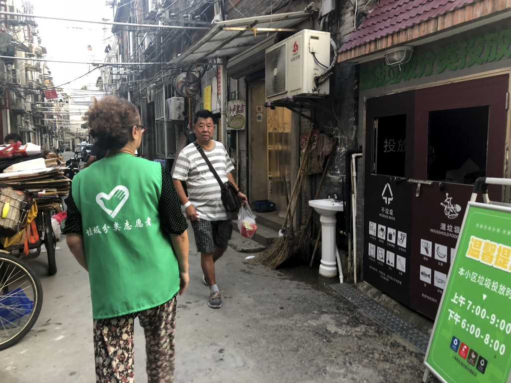 In this July 22, 2019 photo, Zhu Xiaohua, a garbage sorting volunteer, left, stands by the garbage disposal site to help and monitor residents throwin...