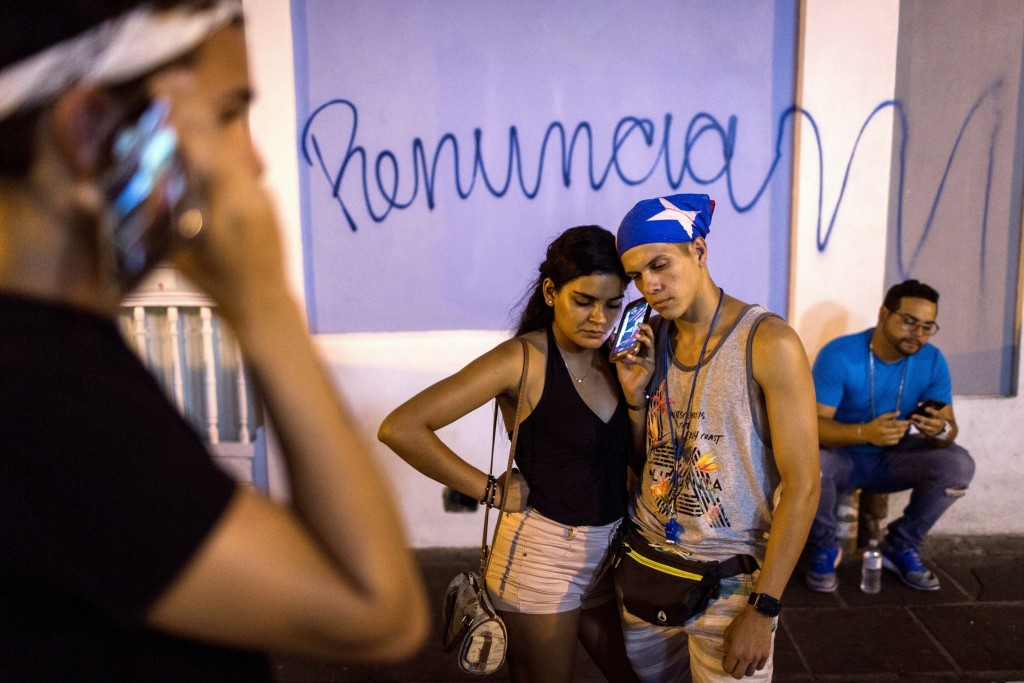 FILE - In this July 24, 2019 file photo, locals listen on a smart phone to the pre-recorded message by Puerto Rico Gov. Ricardo Rossello announcing th...
