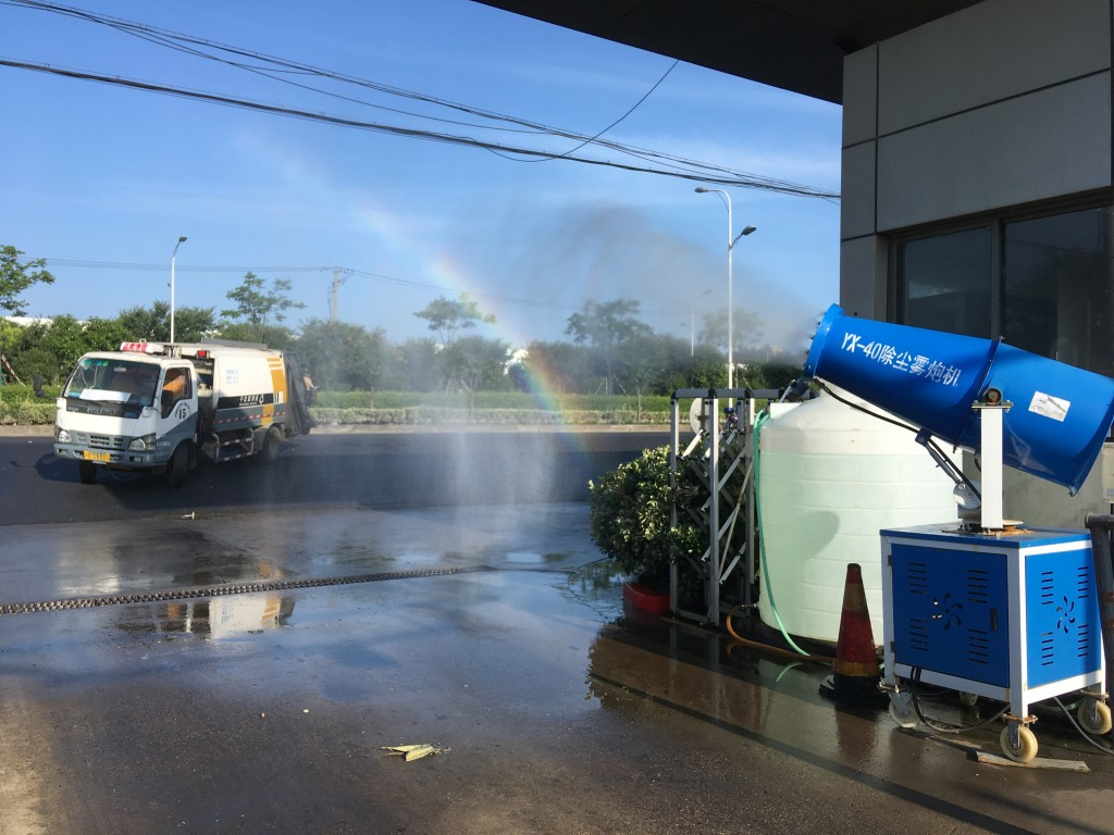 In this  July 23, 2019, photo, a trash collection truck passaes by a rainbow formed by a fog machine used to clean the air at the entrance of a trash ...