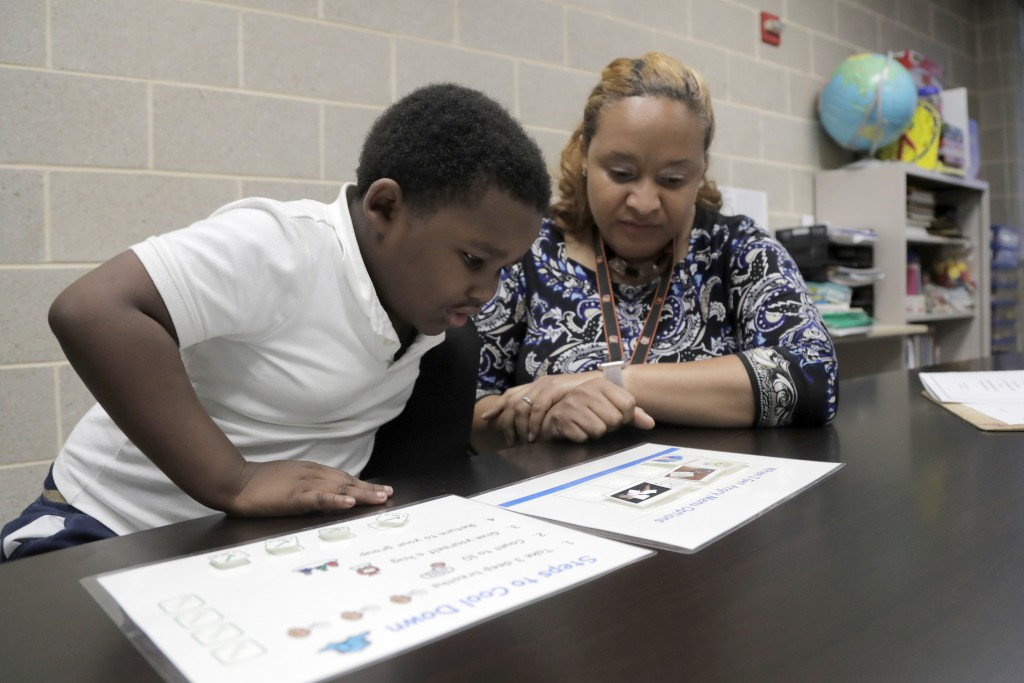In a photo taken Tuesday, July 2, 2019, New Song Community Learning Center principal Lisa Brown, right, works with Eli Stratton, 5, a kindergarten stu...