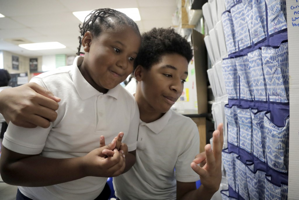 In a photo taken Tuesday, July 2, 2019, Kameryn Wylie, 13, right, a 7th grade student, talks about his project on kinetic energy to 3rd grade student ...