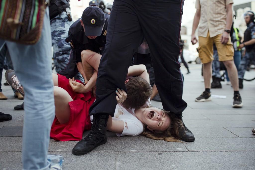 In this photo taken on Saturday, July 27, 2019, Inga Kudracheva screams as her boyfriend Boris Kantorovich lies atop her while police try to detain hi...