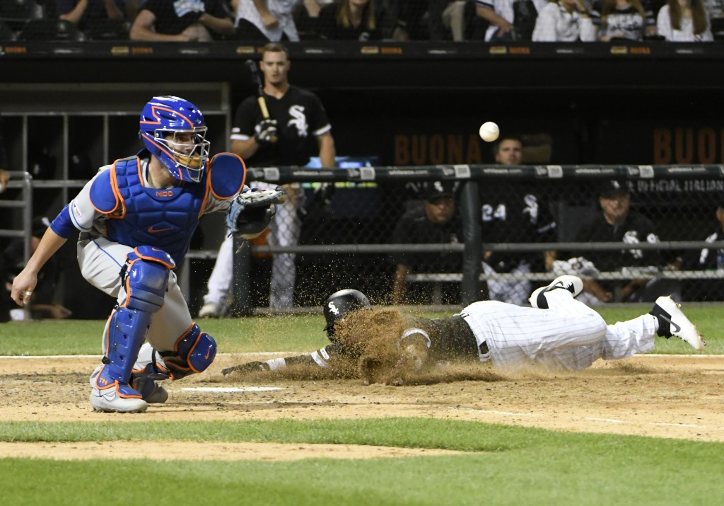 Chicago White Sox's Ryan Goins, right, scores as New York Mets catcher Tomas Nido waits for the throw during the ninth inning of a baseball game, Tues