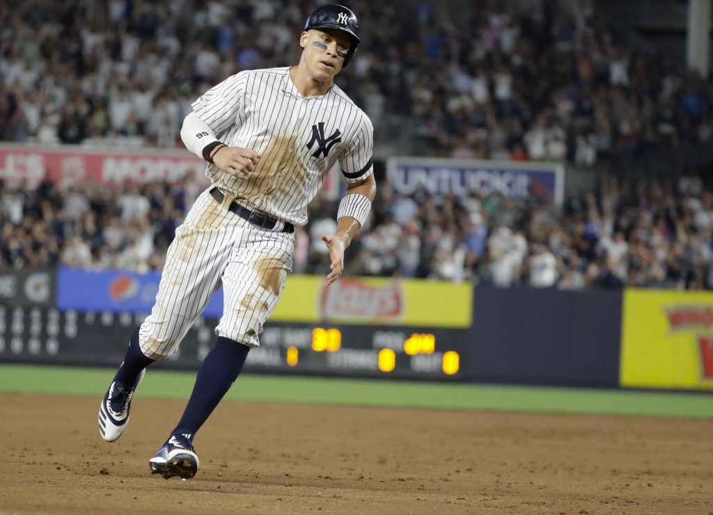 New York Yankees' Aaron Judge runs past third base to score on a double by Edwin Encarnacion during the sixth inning of the team's baseball game again...
