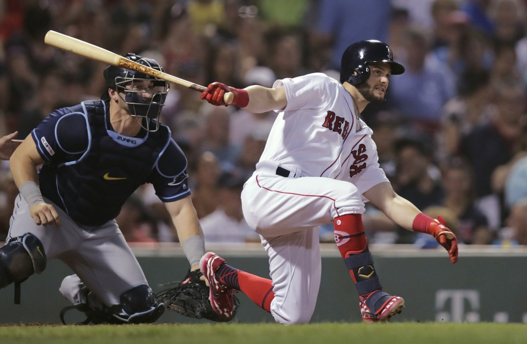 Boston Red Sox's Andrew Benintendi drops to a knee on his RBI single during the third inning of the team's baseball game against the Tampa Bay Rays at...