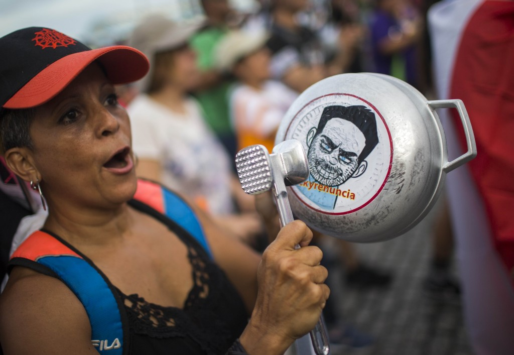 FILE - In this July 19, 2019 file photo, a demonstrator bangs on a pot that has a cartoon drawing of Governor Ricardo Rossello and text the reads in S...