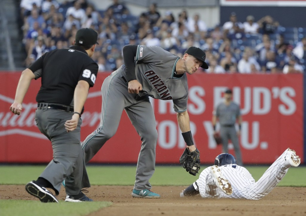 Arizona Diamondbacks shortstop Nick Ahmed, center, tags out New York Yankees' Gio Urshela at second base during the second inning of a baseball game T...