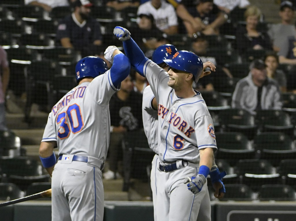 New York Mets' Jeff McNeil (6) is greeted by Michael Conforto (30) after hitting a two-run home run against the Chicago White Sox during the 11th inni