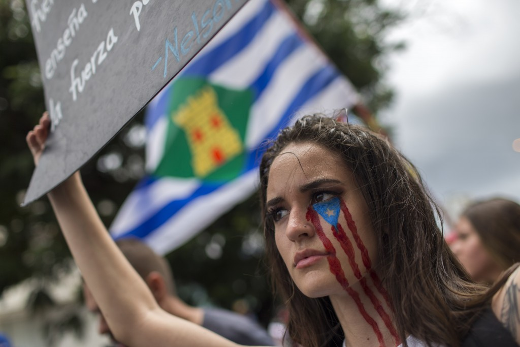 In this July 25, 2019 photo, a young woman takes part in the festivities to celebrate the resignation of Gov. Ricardo Rossello, after weeks of protest...