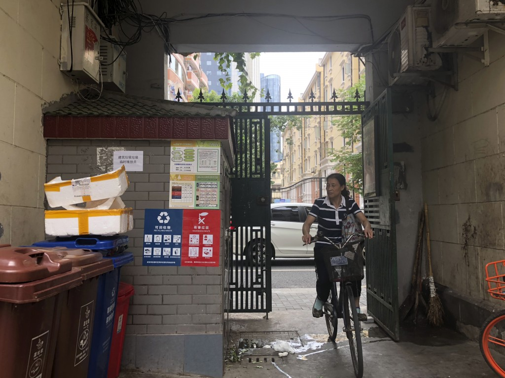 In this  July 22, 2019, photo, a resident cycles past separate waste containers placed in a residential community in Shanghai. China's biggest city ha...