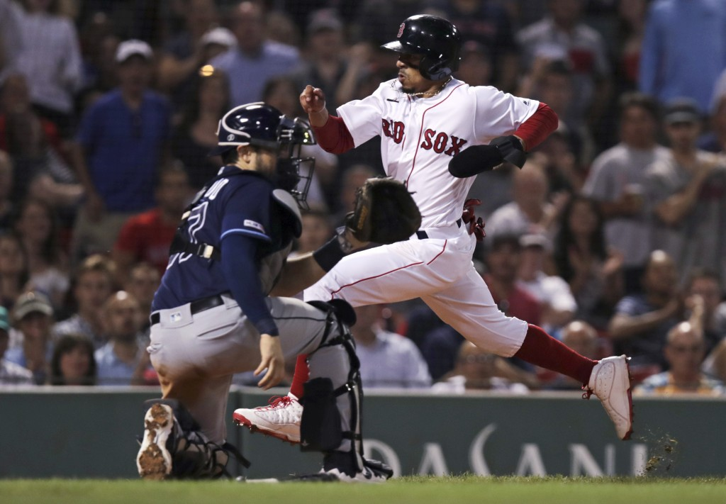 Boston Red Sox's Mookie Betts, right, beats the throw to Tampa Bay Rays catcher Travis d'Arnaud to score on a single by Rafael Devers during the seven...