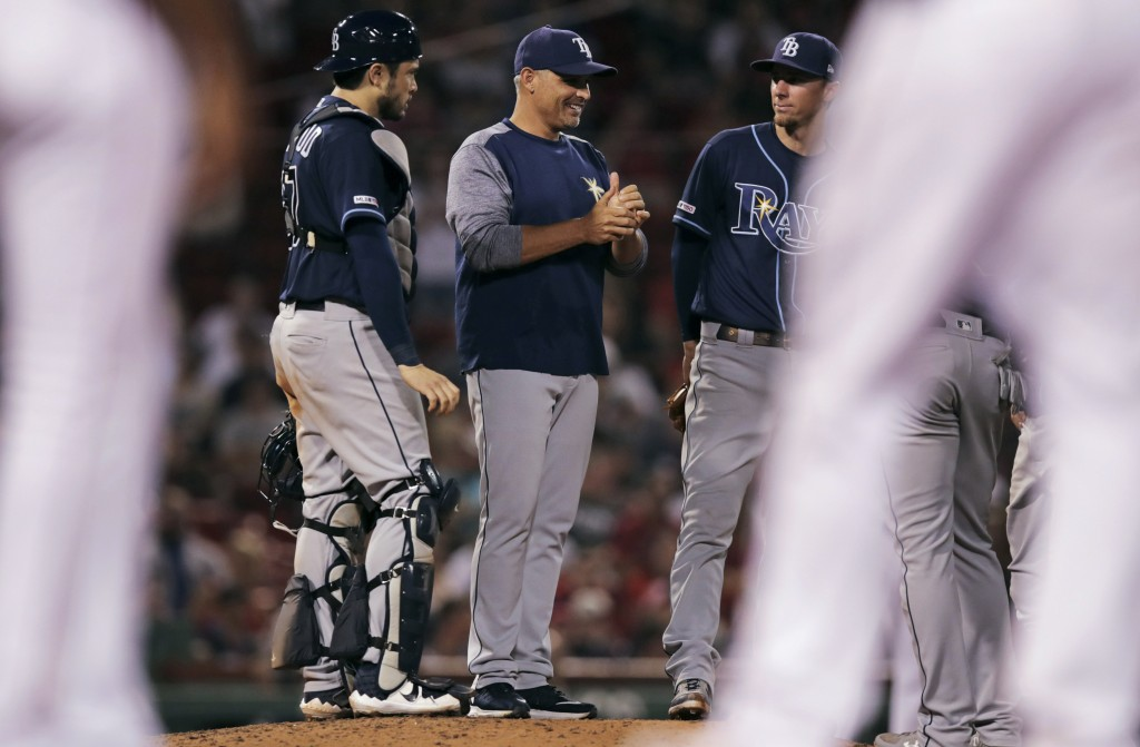 Tampa Bay Rays manager Kevin Cash smiles as he talks with his players during a pitching change in the seventh inning of the team's baseball game again...
