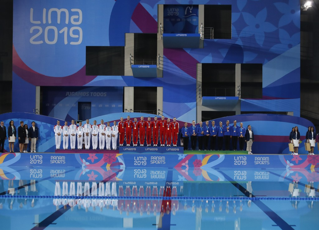 Gold medalists of Canada, center, silver of Mexico, left, and bronze of the United States, listen to Canada's national anthem after the finals of team...