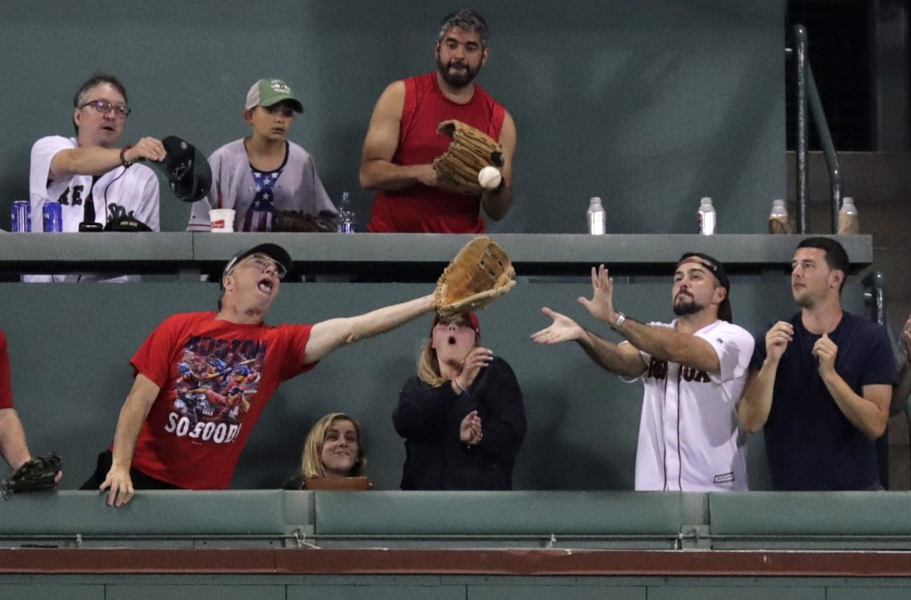 Fans try to catch a solo home run by Tampa Bay Rays' Willy Adames during the sixth inning of the team's baseball game against the Boston Red Sox at Fe...