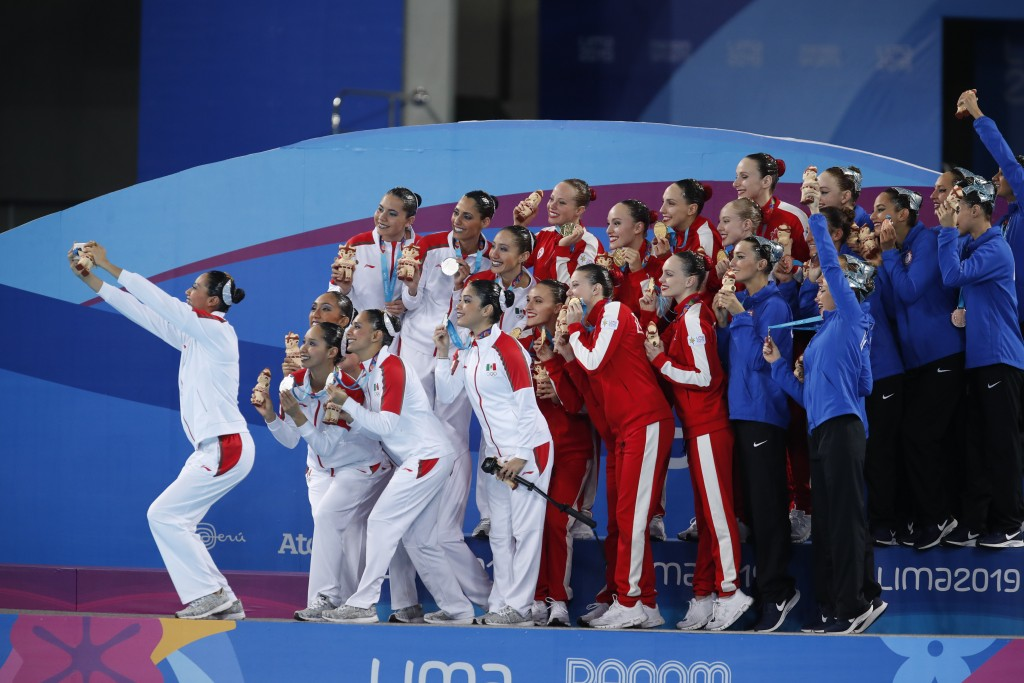 Canada, gold medalists, center, Mexico, silver medalists, left, and the U.S., bronze medalists, right, pose for a selfie after the medals ceremony for...
