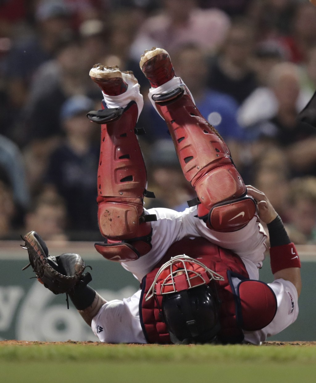 Boston Red Sox catcher Christian Vazquez grabs his knee as he rolls on his back after getting hit with a pitch during the ninth inning of the team's b...