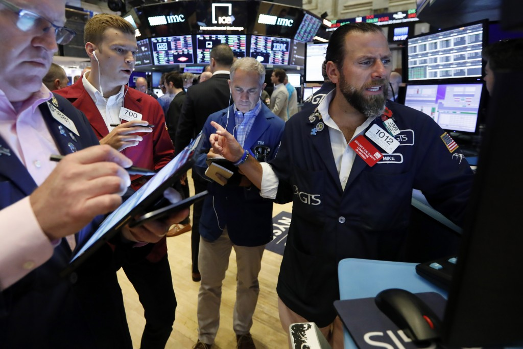 FILE - In this July 19, 2019, file photo specialist Michael Pistillo, right, works with traders at his post on the floor of the New York Stock Exchang