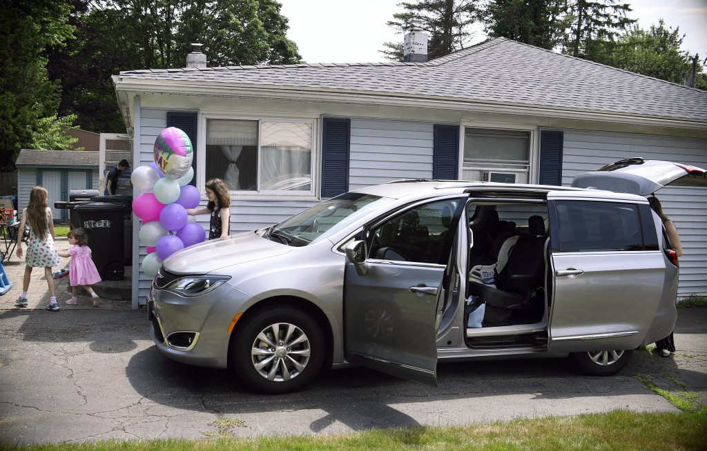 In this Tuesday, July 16, 2019, Melanie Matcheson, right, unloads her Chrysler Pacifica as her son Alexander and daughters Keiley, Caroline, and Georg