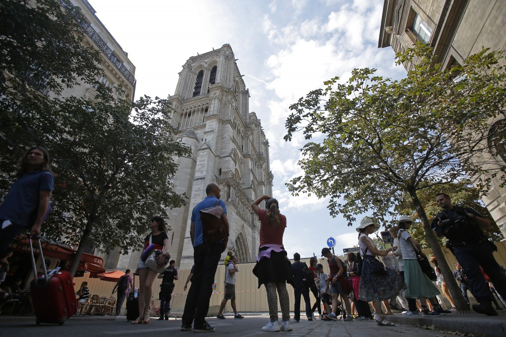 People gather near Notre Dame Cathedral, in Paris, Thursday, Aug. 1, 2019, as the preliminary work begins to repair the fire damage. Paris authorities