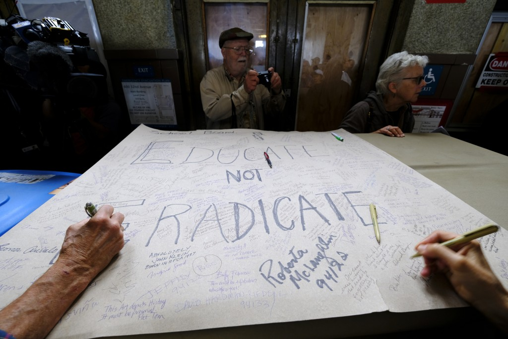 "People put their signatures and messages on a poster that read ""Educate Do Not Eradicate"" while standing below the controversial 13-panel, 1,600-squar..."