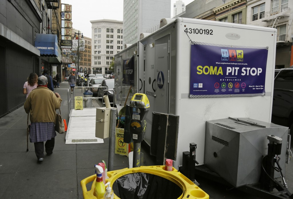 "A woman walks past a ""Pit Stop"" public toilet on Sixth Street, Thursday, Aug. 1, 2019, in San Francisco. A 5-year-old portable toilet program in San F..."