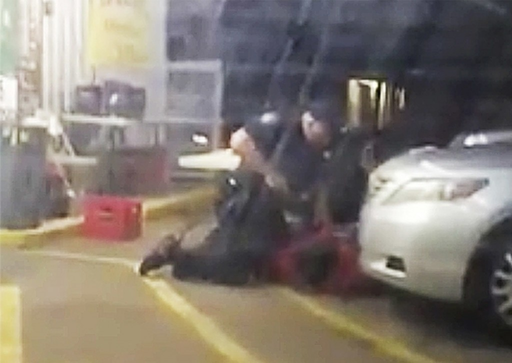 FILE - In this July 5, 2016, file image taken from video, Alton Sterling is restrained by two Baton Rouge police officers, one holding a gun, outside