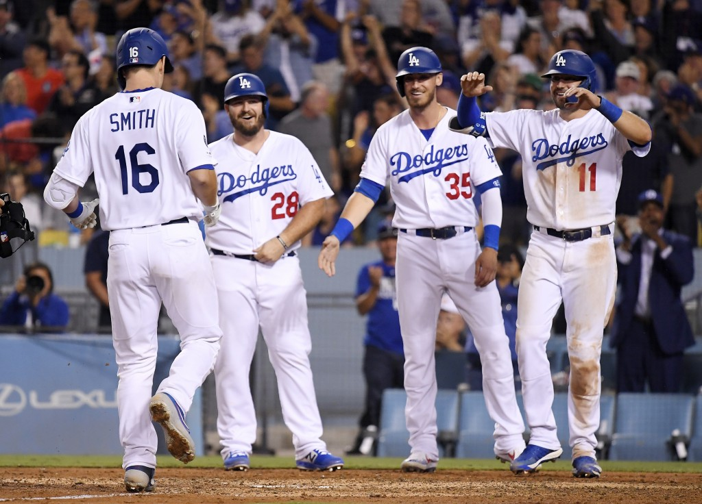 Los Angeles Dodgers' Will Smith, left, scores as teammates Tyler White, Cody Bellinger and A.J. Pollock, from second from left, wait for him after he ...