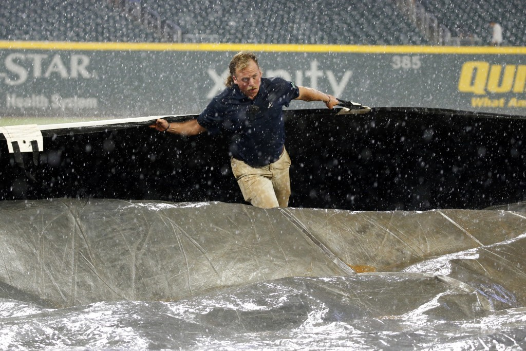 A member of the Atlanta Braves grounds crew works to cover the field during a rain shower in the seventh inning of a baseball game between Cincinnati ...