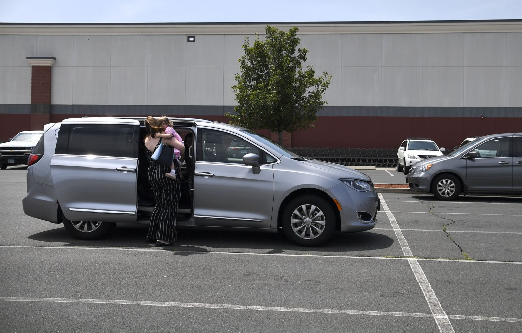 In this Tuesday, July 16, 2019, Melanie Matcheson picks up daughter Caroline out the car seat inside her Chrysler Pacifica in a shopping area parking ...
