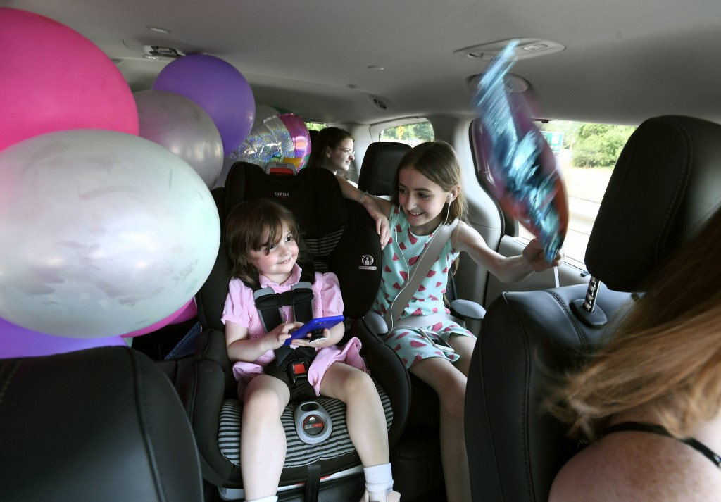 In this Tuesday, July 16, 2019, Sisters Caroline, left, and Keiley play and older sister Georgianna, back looks out a window as their mother, Melanie
