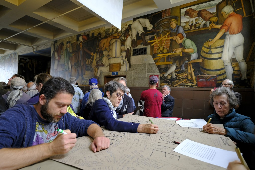 "People put their signatures on a poster that read ""Educate Do Not Eradicate"" while standing near the controversial 13-panel, 1,600-square foot mural, ..."