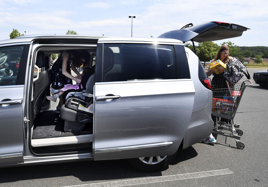 In this Tuesday, July 16, 2019, Melanie Matcheson loads groceries into her Chrysler Pacifica as her daughter Georgianna buckles little sister Caroline