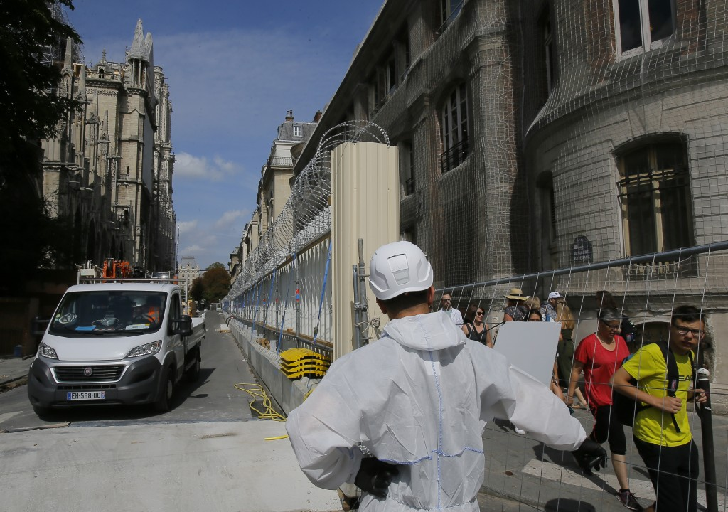 A worker dressed in a white overalls opens the gate on the fence that surround Notre-Dame Cathedral, in Paris, Thursday, Aug. 1, 2019, as the prelimin