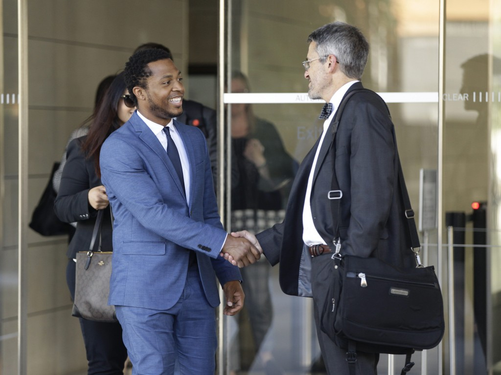 Rapper Marcus Gray, left, shakes hands with his attorney, Michael A. Kahn, right, as they leave the federal courthouse downtown Los Angeles Thursday, ...